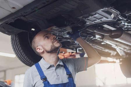 Professional mechanic working under a car in a repair shop, car maintenance and repair concept