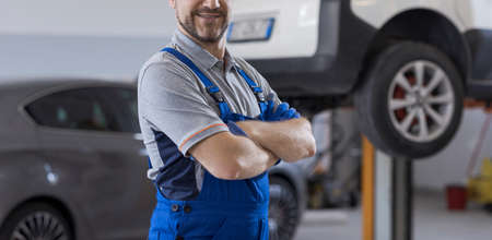 Confident smiling mechanic posing in the auto repair shop, car service and repair concept