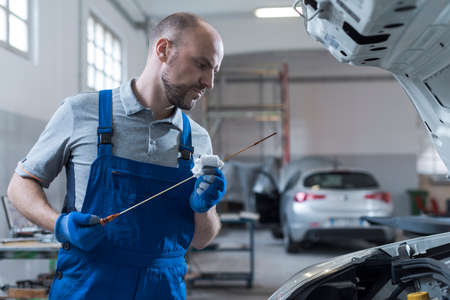 Professional mechanic doing a vehicle inspection, he is checking a car's oil level and quality using a dipstick