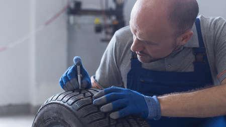 Mechanic checking tire tread depth and wear using a tire gauge, car maintenance concept