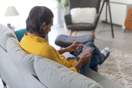 Man sitting on the couch in the living room and connecting online using a digital tablet, lifestyle and technology concept
