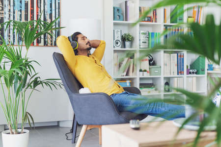 Young man relaxing in the living room at home and listening to music, he is sitting on an armchair and wearing wireless headphones