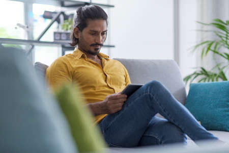 Indian man sitting on the couch at home and connecting online using a digital tablet
