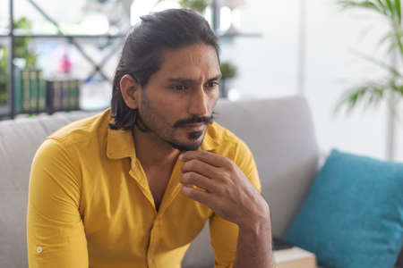 Indian man sitting on the couch at home and thinking with hand on chin 版權商用圖片