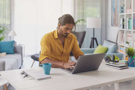 Young man sitting at desk and working with his laptop at home, remote work concept 版權商用圖片