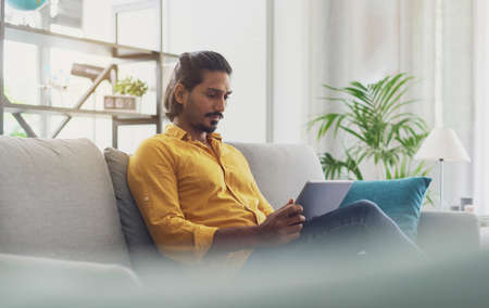 Indian man sitting on the couch at home, he is connecting online and social networking using a digital tablet 版權商用圖片