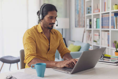 Man sitting at desk and working from home, he is wearing a headset and connecting with his laptop
