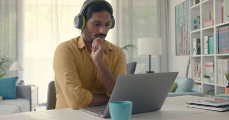Man sitting at desk at home and connecting with his laptop, he is wearing wireless headphones and watching videos online 版權商用圖片