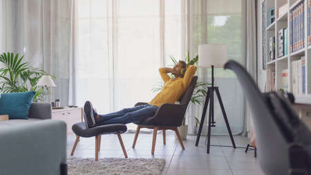 Indian man relaxing in the living room at home and listening to music, he is sitting on an armchair and wearing wireless headphones
