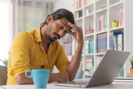 Young stressed man working with a laptop in his office at home, he is having a bad headache 版權商用圖片
