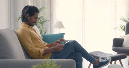Handsome man sitting on the couch at home and connecting with a digital tablet, lifestyle and technology concept