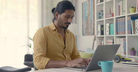 Indian man sitting at desk and typing with his laptop, he is working from home 版權商用圖片