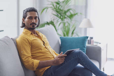 Handsome man relaxing on the couch at home and using a digital tablet, he is looking at camera