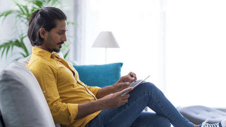Young confident man sitting on the sofa in the living room and connecting online using a digital tablet