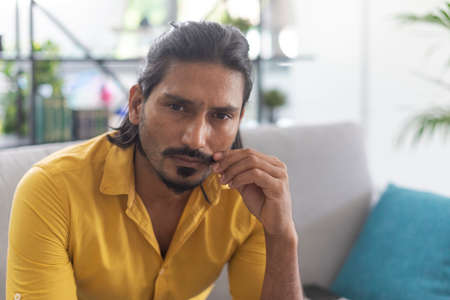 Indian man sitting on the couch at home and adjusting his mustache