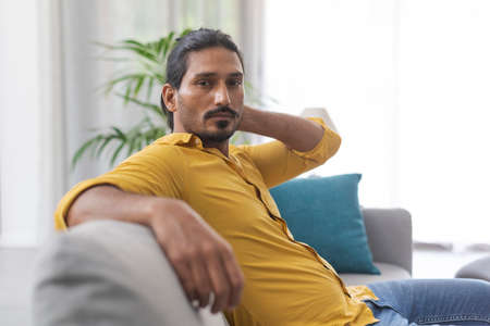 Confident handsome young man relaxing on the couch at home and looking at camera