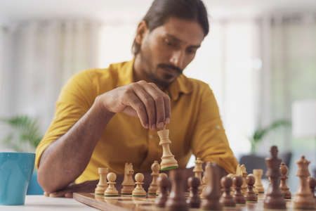 Man playing chess at home in the living room, he is moving a piece on the chessboard and thinking, strategy games concept 版權商用圖片
