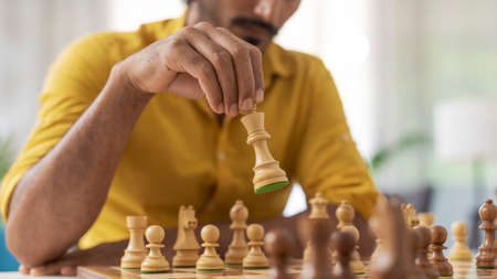 Man playing chess at home, he is moving a piece on the chessboard, strategy games concept