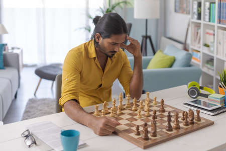 Young man sitting at desk and playing chess, strategy and challenge concept 版權商用圖片