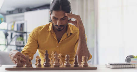 Smart man playing chess at home, he is moving pieces on the chessboard and thinking, strategy games concept