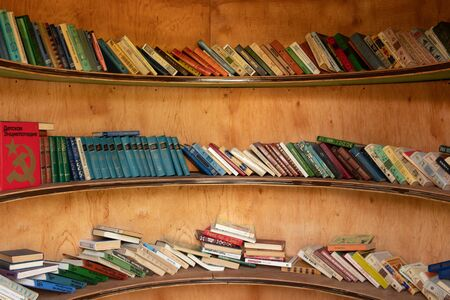 Street library. A large number of books lie on the shelves. Spherical bookcase.