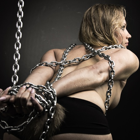 Beautiful chained and nude girl bent away from the camera, looking away photo
