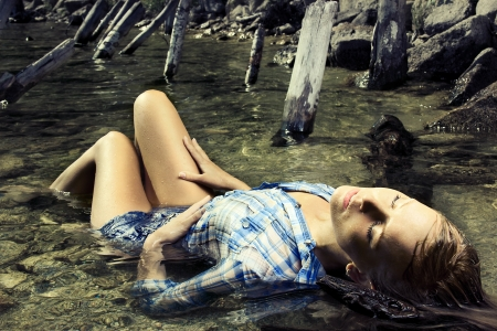 Fashion photo of young beautiful woman lying in water with eyes closed photo