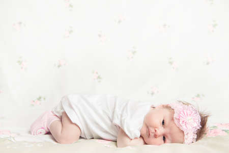 Beautiful newborn girl holding a flower on a white background photo