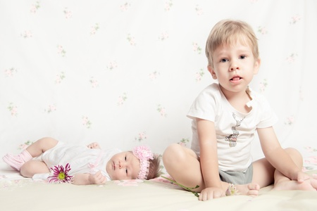 Beautiful newborn girl holding a flower and young boy sitting on a white background photo