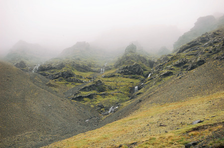 Iceland mountains in a fog with small waterfalls Stock Photo