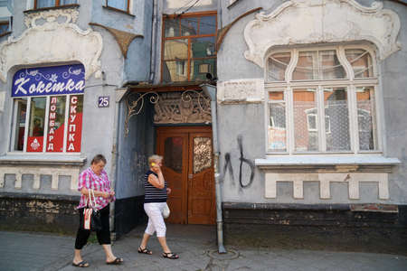 Two women walk near an old German house. 版權商用圖片