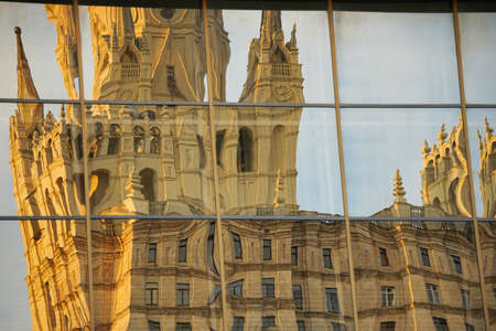 A large historic building is reflected and distorted in mirrors