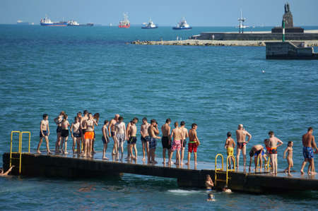 Teenagers and tourists sunbathe on the pier and swim in the sea.