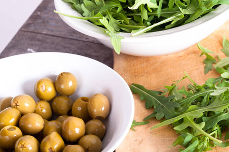 Arugula and olives lie in porcelain bowls  photo