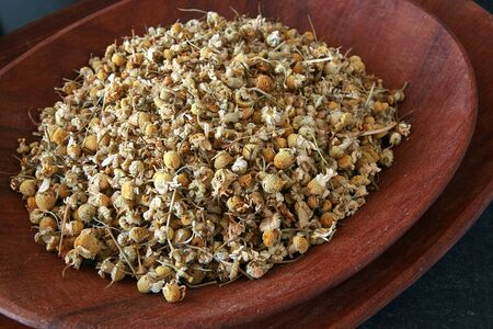 dried herbs: Dried herbs sprinkled in a wooden bowl