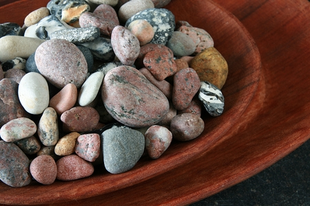 differently: Large number of differently colored stones in a wooden bowl