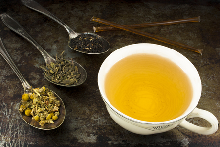 loose leaf: A cup of brewed green tea with honey sticks and loose leaf tea leaves