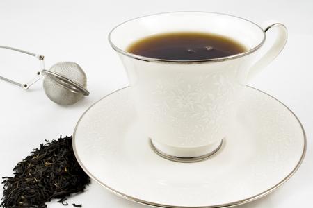 Ein gebrühten Tasse schwarzen Tee in einer Porzellanschale neben einem Sieb und Teeblätter mit Platz für Text