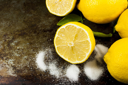 room for text: A sliced lemon and three whole lemons with sugar and room for text Stock Photo