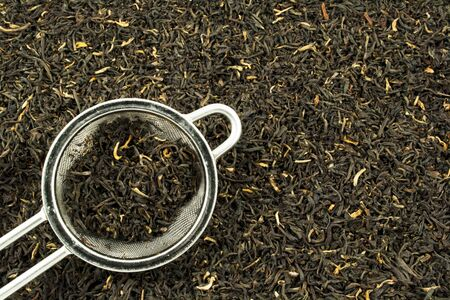 tea strainer: Tea leaves and strainer filling the frame