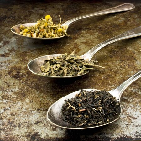 rustic: Black, green and herbal tea leaves in silver spoons on a rustic background.