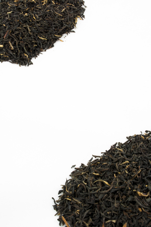 loose leaf: Two piles of loose leaf black tea against a white background with room for text in the middle. Stock Photo