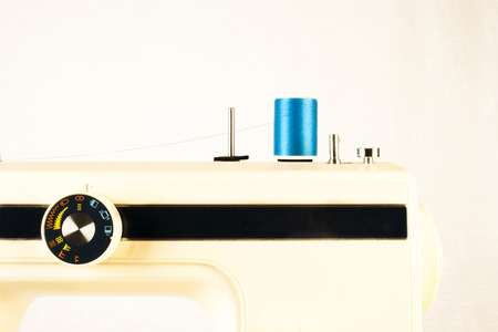 stitching machine: Closeup of a vintage sewing machine with blue thread. Retro style Stock Photo
