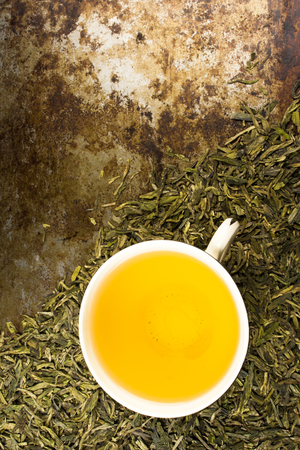 room for text: A cup of brewed green tea with green tea leaves against a rustic background with room for text Stock Photo