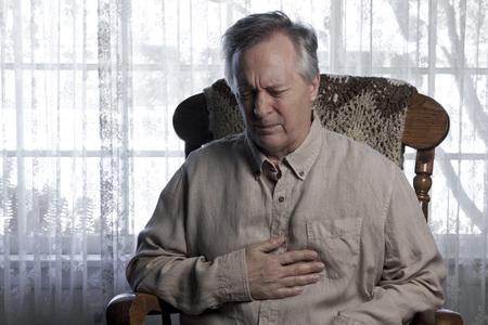 angina: Hombre mayor que sostiene el pecho y haciendo una mueca con la angina de pecho mientras se sienta en una silla mecedora