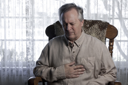 angina: Older man holding his chest and wincing with angina as he sits in a rocking chair