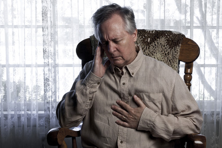 ulcers: Older man sitting in a rocking chair and wincing holding his chest and head
