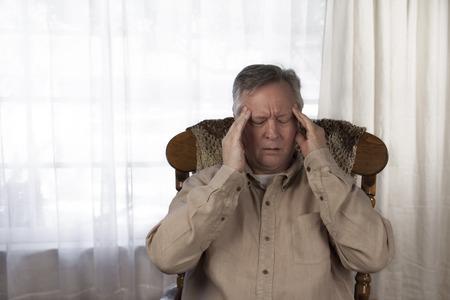 soreness: Elderly man holding his hands to his head as he suffers from a headache or migraine. Sitting at home in a rocking chair