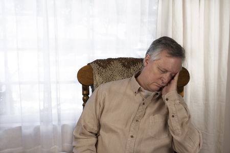 drowsiness: Older man suffering from the symptoms of fatigue. Sitting in a rocking chair at home. Stock Photo