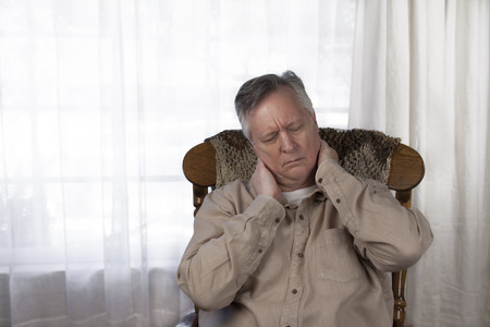 senior man on a neck pain: Older man suffering from the symptoms of neck pain. Sitting in a rocking chair at home. Stock Photo